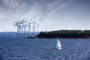 Big group of wind turbines on the bay with a small sailboat sailing in the foreground.